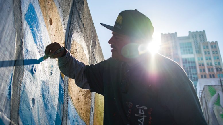 """Markos Egure works on the """"Humanity"""" mural Aug. 28, a work made by the ARTners Collaborative. The mural is located on Improv Alley between 7th and 8th streets. Jason Pierce 