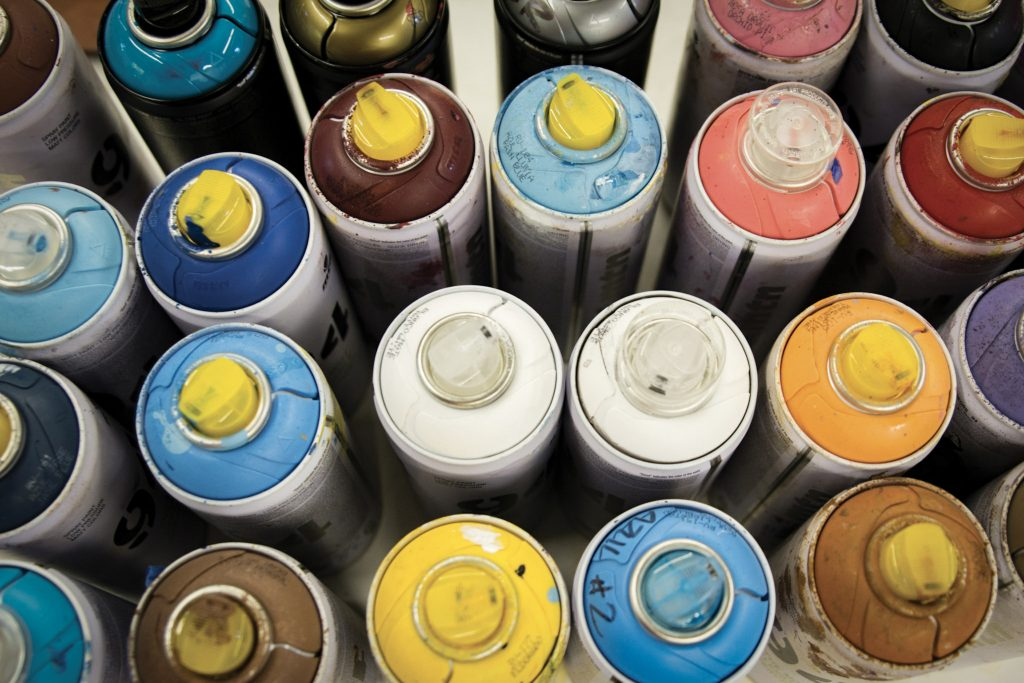Spray paint cans are some of the supplies kept on hand in Stephanie Taylor's studio. Her mural was originally painted with automotive spray paint.