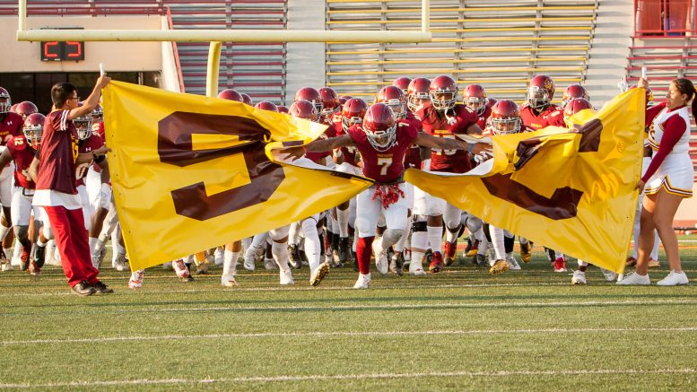 City College football team breaks through the SCC banner to start the game against Modesto Junior College at Hughes Stadium on Sept. 16. ©2017 Dianne Rose
